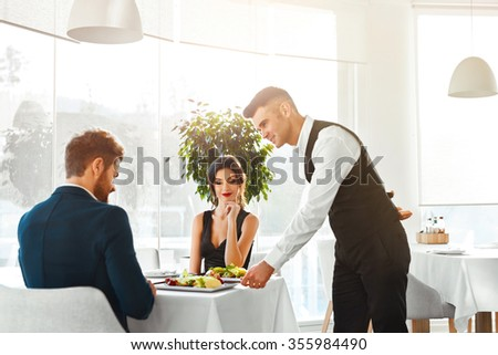 Happy Couple In Love Having Romantic Dinner In Luxury Gourmet Restaurant. Waiter Serving Meal. People Celebrating Anniversary Or Valentine's Day. Romance, Relationship Concept. Healthy Food Eating. - stock photo