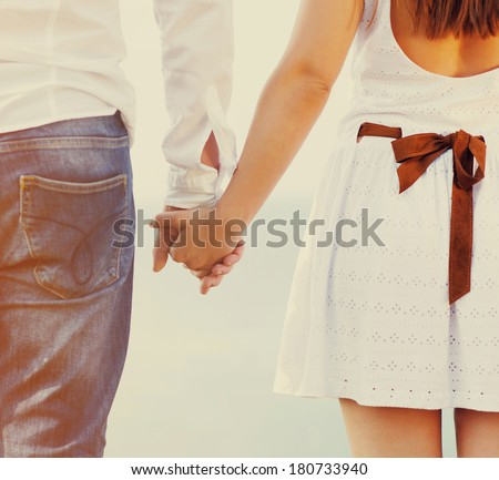 Happy couple in love holding hands walking away near the sea - stock photo