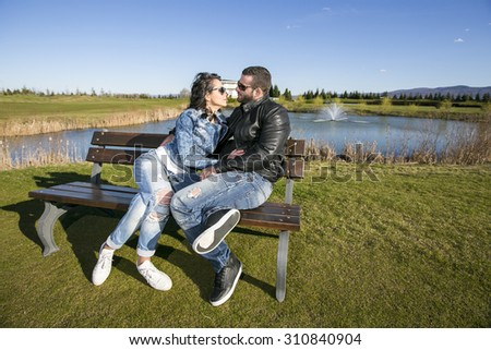 Happy couple in love In the park sit on the bench.  Dressed in black leather jackets.