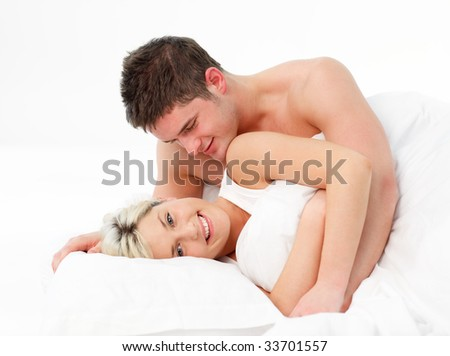 Happy couple in love lying in bed