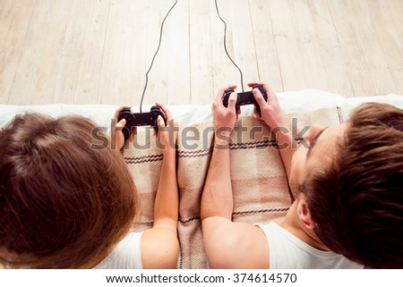 Happy couple in love playing video games with joysticks on the bed - stock photo