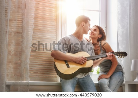 Happy couple in love. Stunning sensual portrait of young stylish fashion couple indoors. Young man playing guitar for his beloved girl. - stock photo