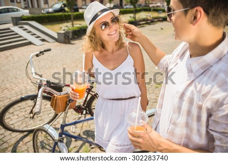 Happy couple in love with bicycles and glasses of juice on the city street looking to each other. - stock photo