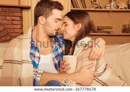 Happy couple in love with plaid and cup embracing each other - stock photo
