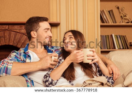 Happy couple in love with plaid and cups relaxing on the sofa - stock photo