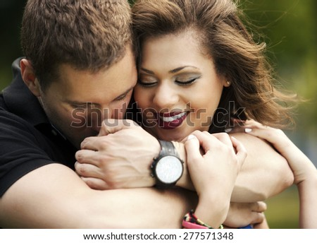 Happy couple in love, young man hugging young woman from behind - stock photo