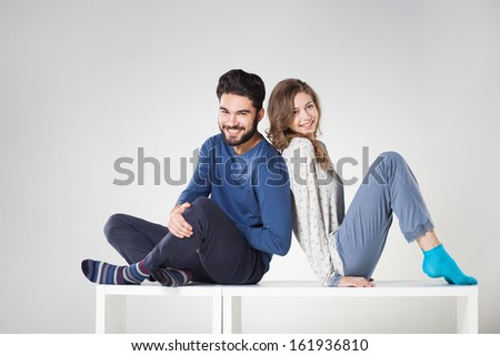 Happy couple in pajamas posing in the studio - stock photo