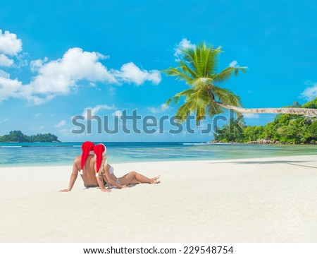 Happy couple in santa hats at tropical sandy palm beach, christmas and new years vacation concept, Seychelles, Mahe island, Baie Lazare - stock photo