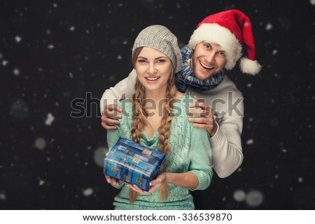 Happy Couple in Santa's Hat with Christmas and New Year Gift on dark and snowy background - stock photo