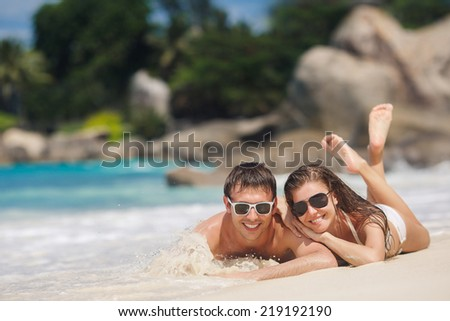 Happy Couple in Sunglasses having fun on the Beach. Summer Vacation. Laughing Family enjoying Nature over Sea Background. Attractive Man and Woman at the Beach. Sun tan. Maldives. Seychelles.
