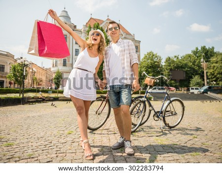 Happy couple in sunglasses on the city square. Woman holding shopping bags and having fun. - stock photo