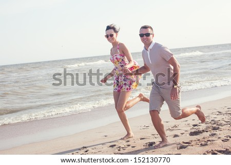 Happy couple in sunglasses. Run on the beach holding hands. Dynamic shot outdoors - stock photo