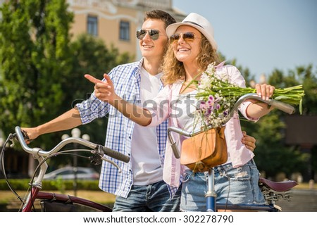 Happy couple in sunglasses with bicycles on the city street. Woman pointing away. - stock photo