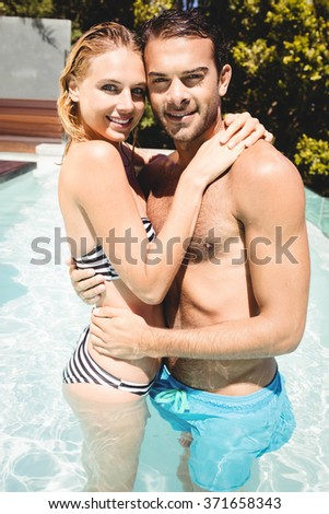 Happy couple in the pool embracing and looking at the camera