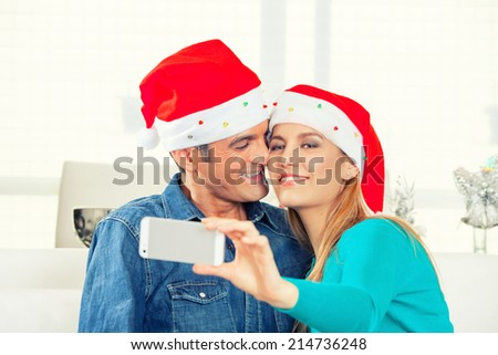 Happy couple in their 30s making a selfie for Christmas at home. - stock photo