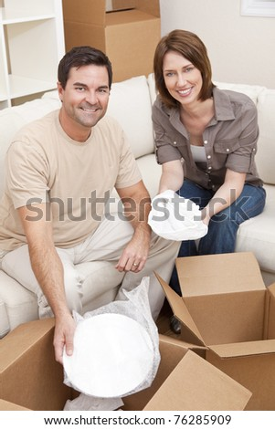 Happy couple in their thirties unpacking or packing boxes and moving into a new home. - stock photo