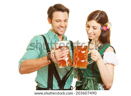 Happy couple in traditional outfit drinking beer in Bavaria at Oktoberfest - stock photo