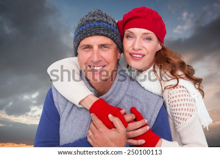 Happy couple in warm clothing against blue and orange sky with clouds
