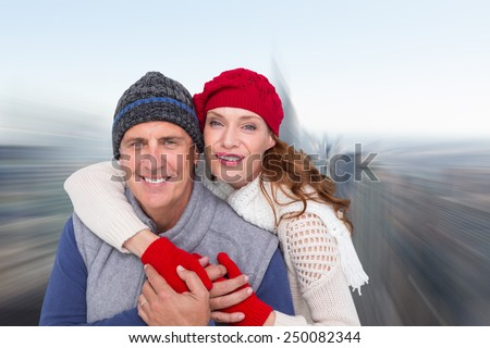 Happy couple in warm clothing against city skyline