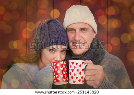 Happy couple in warm clothing holding mugs against close up of christmas lights