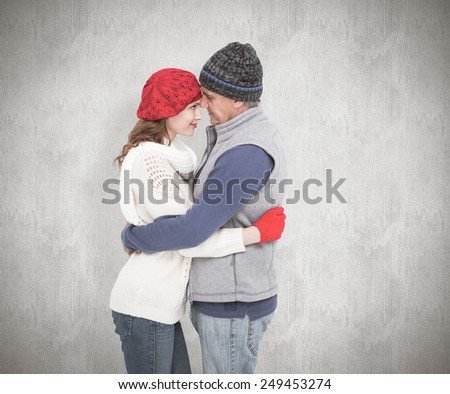 Happy couple in warm clothing hugging against white background