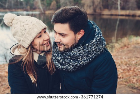 happy couple in warm knitted hat and scarf walking outdoor in autumn forest, cozy mood
