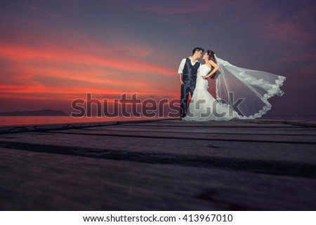 Happy couple in wedding dress and smile on the wood bridge - stock photo
