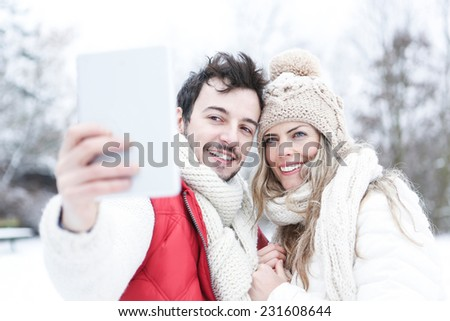 Happy couple in winter taking pictures of themselves with tablet PC - stock photo