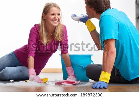 Happy couple is cleaning together and having good time - stock photo