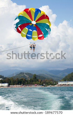 happy couple is flying on a parachute behind a boat