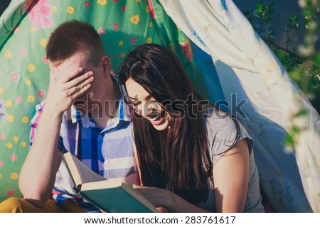 happy couple is reading the book in the tent in summer