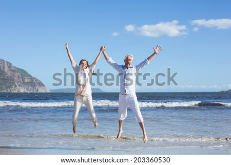 Happy couple jumping up barefoot on the beach on a sunny day - stock photo