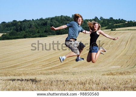 happy couple jumps outdoors in summer - stock photo