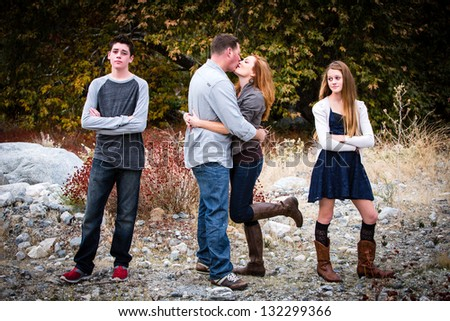 Happy couple kissing as their teen aged children look on in disgust