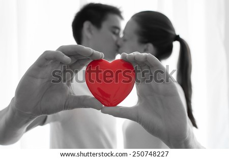 Happy couple kissing behind a red heart
