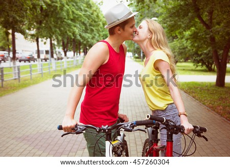 Happy couple kissing during a bicycle ride outdoors at summer - stock photo