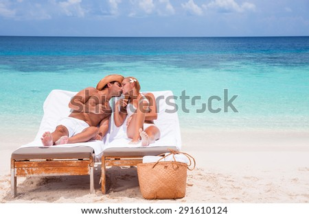 Happy couple kissing on beach resort, tanning on sunbed and eating tasty sweet ice cream, enjoying summer time on beautiful sea coast - stock photo