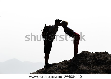 Happy couple kissing on mountain summit silhouette. Hikers success on mountain top kissing, success and healthy lifestyle, kiss romantic beautiful inspirational landscape. - stock photo