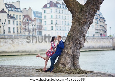 Happy couple kissing on the bank of the Seine in Paris. Tourists enjoying their vacation in France. Romantic date or traveling couple concept - stock photo