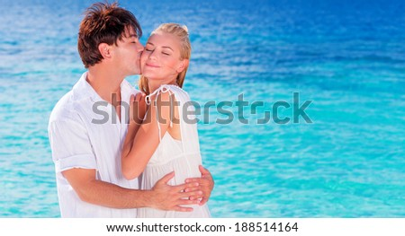 Happy couple kissing on the beach, young family in love spending honeymoon vacation on an islands, cheerful active young people having fun at summer travels, joy of life concept - stock photo
