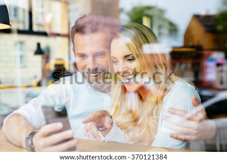 Happy couple laughing at coffee shop, looking on smartphone - stock photo