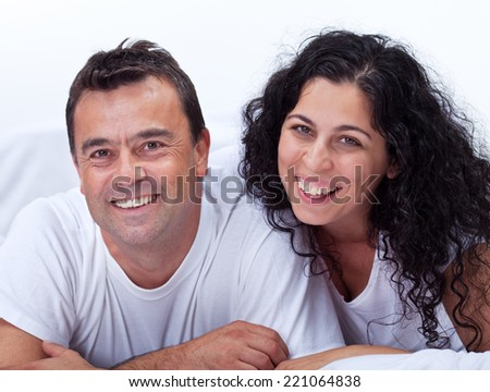 Happy couple laughing together wearing white - stock photo