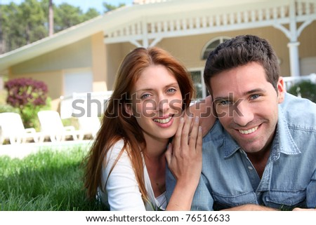 Happy couple laying down in their home garden - stock photo