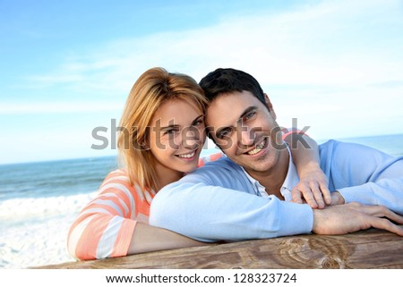 Happy couple leaning on a fence by the sea