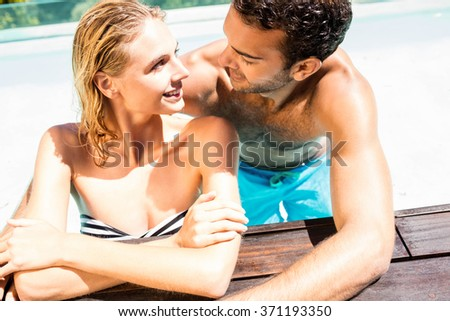 Happy couple leaning on pool edge in a sunny day - stock photo