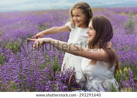 Happy couple little girl with her mother are in a lavender field holding bouquet of purple flowers - stock photo