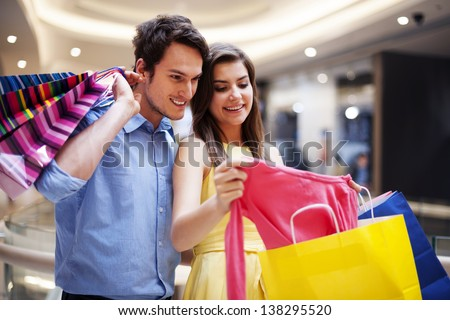 Happy couple looking at a new shirt - stock photo