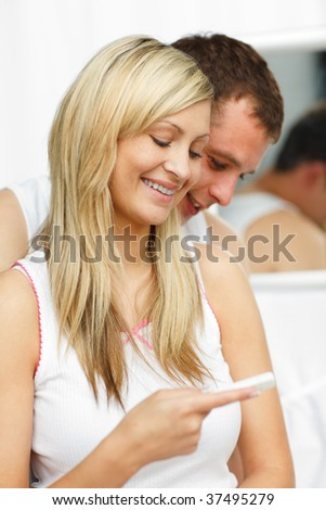 Happy couple looking at a pregnancy test in bathroom