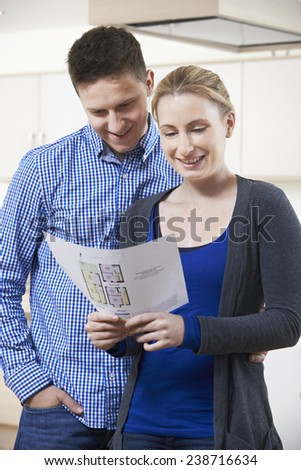 Happy Couple Looking At Details For Property They Hope To Buy - stock photo