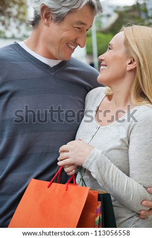 Happy couple looking at each other as woman holding shopping bags - stock photo